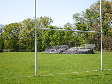 Green field with small, stadium bleachers surrounded by trees