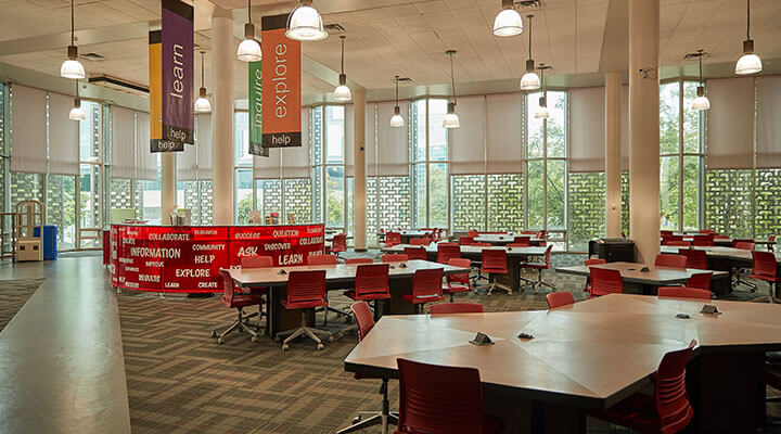 Large, windowed library with collaborative desks and red chairs