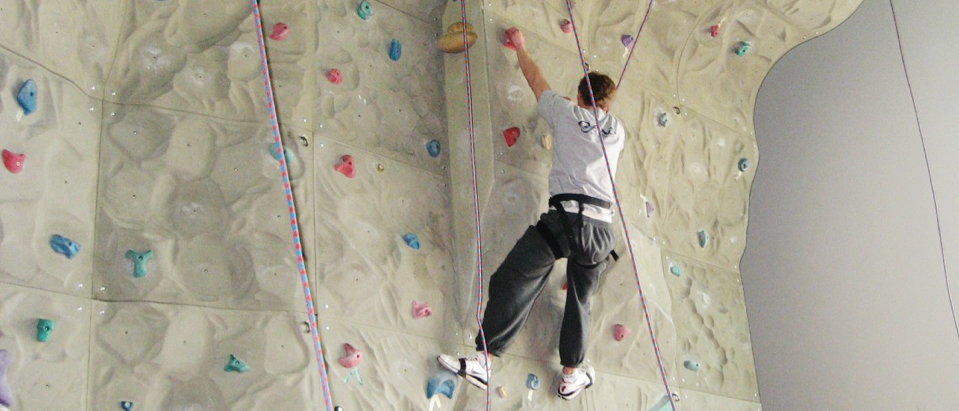 McMaster student on rock climbing wall in McMaster gym facility