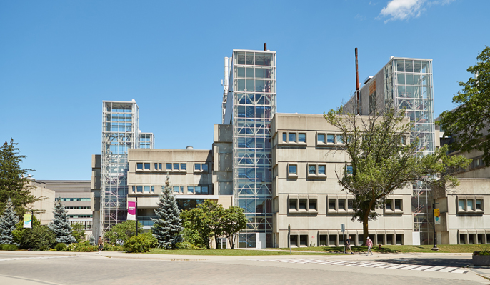 Modern-style cement health sciences building with trees in front