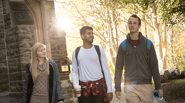 Friends walking on campus in the backdrop of a historic stone building and towering trees