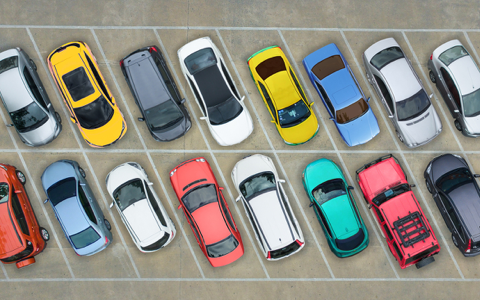 multicoloured cars parked in two diagonal rows