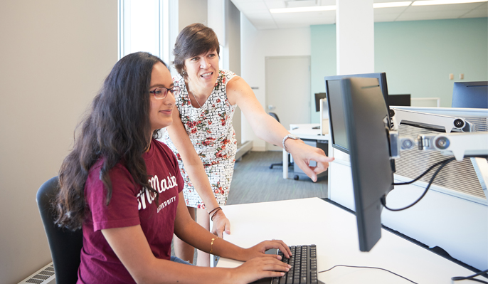 Student and professor in Social Sciences building at McMaster University
