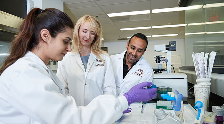Students and professor in lab coats performing experiments in McMaster lab