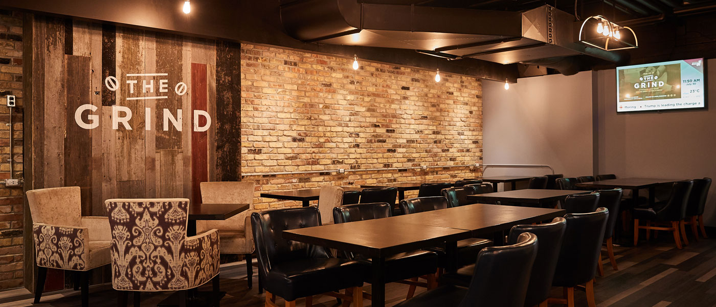 Campus restaurant with brick and wood backsplash and tables with cushioned chairs