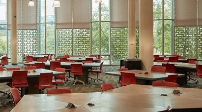 Study at McMaster - McMaster Mills Learning Commons - Empty McMaster study room with collaborative desks and red chairs