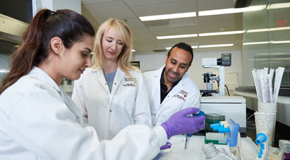 Work at McMaster - Group of McMaster students in white lab coats conducting science experiment