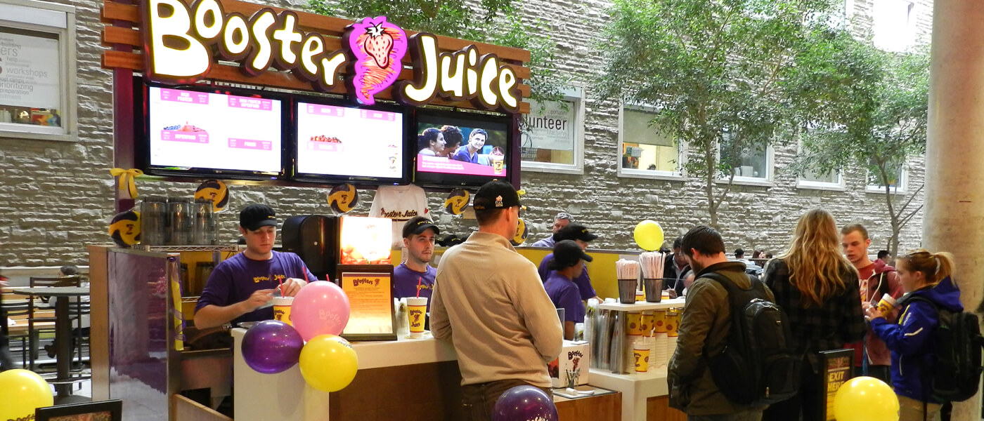 McMaster students surrounding Booster Juice cafe in brightly lit area