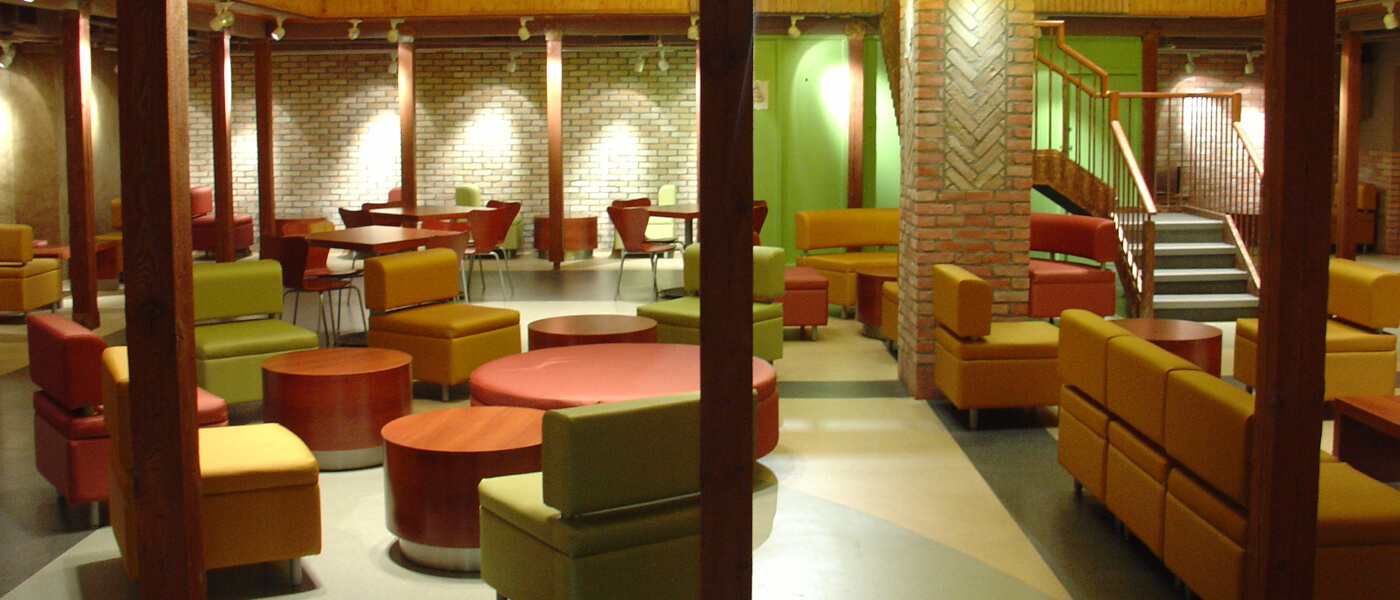 Bridges Cafe - Lounge area with brick walls and padded couches and tables